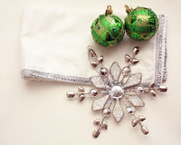 Metal snow flake and two green Christmas balls on a white and silver napkin Royalty Free Stock Image