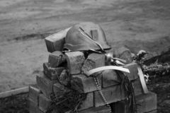 Metal soldiers helmet lying on pile of concrete grey bricks. Soldiers Military Ammunition black and white picture royalty free stock image