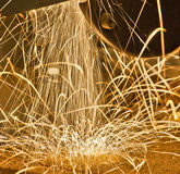 Metal Sparks Dance Across a Workbench. Sparks emanating from a workshop grinder and dancing across the top of the workbench. Photo made 26 July 2012 Royalty Free Stock Photography