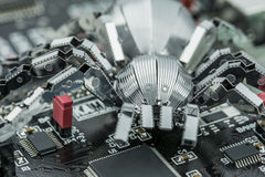 A metal spider on a PCB. A metal spider standing on a printed circuit board Stock Photography