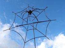 Metal spider in a web against the sky Stock Image