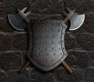 Metal spiked shield and two crossed battle axes on stone wall 3d illustration Royalty Free Stock Photo