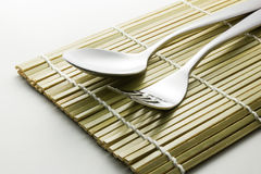 Metal spoon and fork on bamboo mat. Stock Image