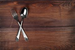 Metal spoon and fork are crossed on wooden background royalty free stock photos