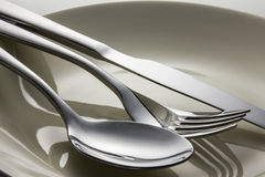 Metal spoon and fork on dish. Stock Photo