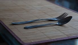 Spoon and fork lying on a bamboo mat stock photos