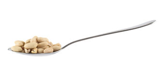 Metal spoon full of peanuts isolated. Side view metal spoon full of peanuts isolated over white background Royalty Free Stock Images