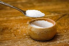 Metal spoon with sea salt and small wooden bowl on wooden table. Macro photography in rustic ambient stock photos