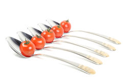 Metal spoons with tomatos Royalty Free Stock Images