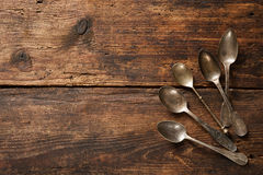 Metal spoons on wooden table Stock Photos