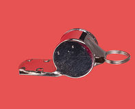 Metal sports whistle over red Stock Photo