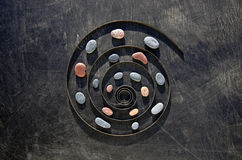 Metal spring spiral and sea stone time concept. Still-life in black royalty free stock images