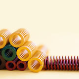 Metal springs colorful steel spirals coil with different hardness flexibility sizes. yellow background, soft focus. Shallow depth of field Stock Images