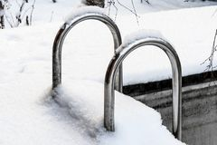 Metal staircase in the outdoor pool covered with snow stock images