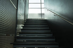 Metal stairs inside building leading window Royalty Free Stock Image