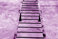 Metal stairway on cement wall in purple tone. Stock Photo