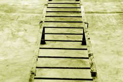 Metal stairway on cement wall in yellow tone. royalty free stock image