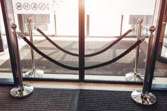 Metal stand barricade with velvet rope in front of glass doors. Closed entrance to shopping center. No entry Stock Photos