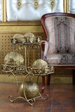 Metal stand with golden balls near chair Stock Image