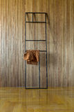 Metal stand with pullover. Black metal frame stand which leans on the wooden wall. Brown pullover hangs on the stand. On the floor there is a parquet. Indoors Stock Photos
