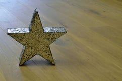 Metal star. On wooden floor Royalty Free Stock Image