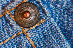 Metal stave on jeans Royalty Free Stock Photos