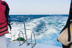 Metal steel ladders near lifejackets on back teak deck of a motor yacht. Sailing on a sea stock photo