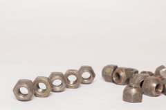 Metal and steel nuts on white background. Several metal and steel nuts on white background Royalty Free Stock Photo