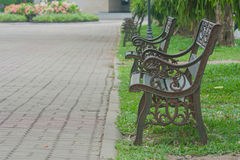 Metal steel old fashioned bench chair on green grass. Royalty Free Stock Photography