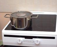 Metal steel saucepan on modern kitchen electric stove Stock Photo