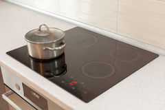 Metal steel saucepan in modern kitchen with induction stove. Royalty Free Stock Photo