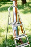 Metal stepladder in a green garden at sunny day. Metal stepladder in a green garden at sunny day Royalty Free Stock Photo