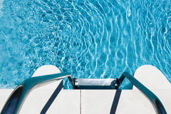 Metal steps into inviting blue pool Stock Images