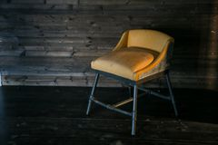 Metal stool with soft upholstery in loft style against a wooden wall. Free space for text. royalty free stock images