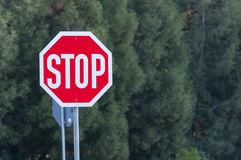 Metal stop road sign. Stop road sign at forest before trees Royalty Free Stock Photography