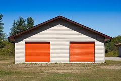 Metal storage building. Large storage shed with orange doors Royalty Free Stock Photo