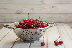 Metal strainer with ripe berries and cherry on wooden background. Colander filled with cherries over a rustic board. Metal strainer or bowl with ripe berries Stock Image