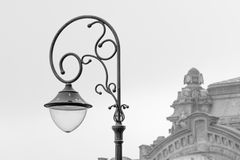 Metal street lamp with building behind. Black and white view of Stock Photo