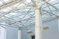 Metal structure of a glass roof in a building. With lighting on poles Royalty Free Stock Images