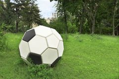Metal stylized soccer ball on a green lawn. In a clearing among the city park royalty free stock image