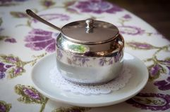 Metal sugar bowl with a lid and a spoon . Royalty Free Stock Photos