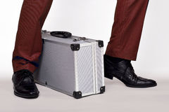 Metal suitcase. Between legs, on the run Royalty Free Stock Images