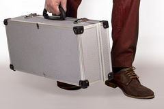 Metal suitcase. Man holding a metal suitcase on white background Stock Images