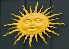 Metal sun on green wood background Stock Image