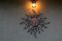 Metal sunburst on stucco wall and glow of lantern Royalty Free Stock Photo