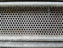 Metal surface with round holes and straight line borders above and below. royalty free stock photography