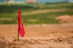 Metal survey peg with red flag on construction site.  stock image