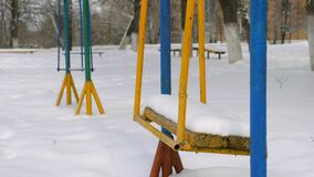 Metal swing in the snow. Snow covered swing at a playground in winter stock video