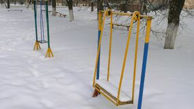 Metal swing in the snow. Snow covered swing at a playground in winter stock footage