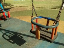 Two empty swings in park on fall morning royalty free stock image